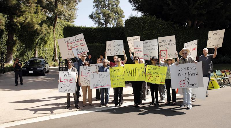 In this Oct. 1, 2013 photo, friends and family of veteran radio personality Casey Kasem stage a protest outside his home in Beverly Hills, Calif. Kasem's children from a former marriage, his brother and friends who want to see him have have been denied any contact with him by his current wife, Jean Kasem. The three adult children of the radio host have filed a legal petition for conservatorship on Monday, Oct. 7, 2013, to gain control of his health care. (Photo by Todd Williamson/Invision/AP)