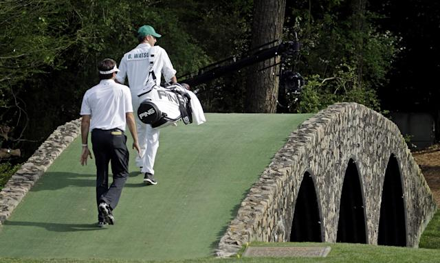 Bubba Watson walks across the Hogan Bridge with his caddie Ted Scott during the fourth round of the Masters golf tournament Sunday, April 13, 2014, in Augusta, Ga. (AP Photo/Darron Cummings)