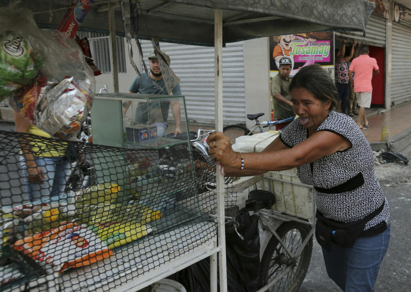 A street vendor pushes her cart away from Venezuelan Bolivarian National Guards firing rubber bullets at people protesting their presence in Urena, Venezuela, Sunday, Feb. 24, 2019, on the border with Colombia. A U.S.-backed drive to deliver foreign aid to Venezuela on Saturday met strong resistance as troops loyal to President Nicolas Maduro blocked the convoys at the border and fired tear gas on protesters. (AP Photo/Fernando Llano)