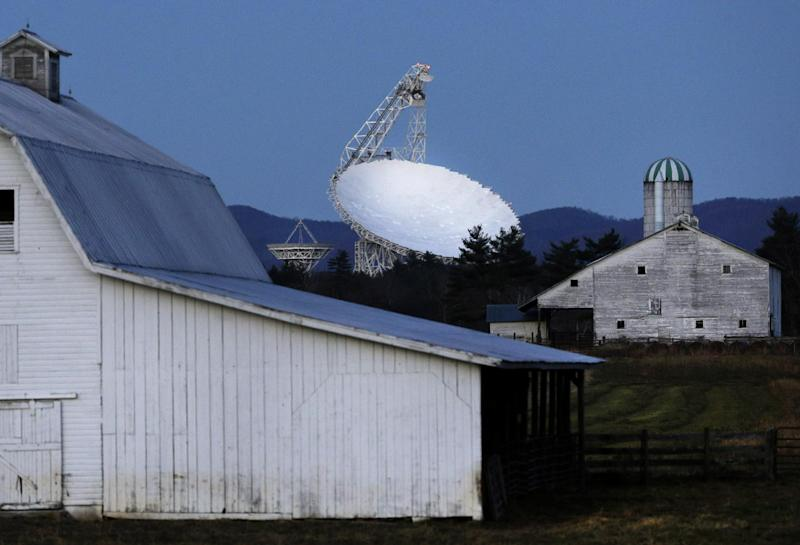 In this Nov. 14, 2013 photo, the Robert C. Byrd Green Bank Telescope towers over farmland as dusk falls in Green Bank, W.Va. Officials at the National Radio Astronomy Observatory chose the site for its remote location and mountainous surroundings, which help to keep distant radio waves outside of the quiet zone at bay, while interference inside the zone is restricted by state and federal laws. The National Radio Quiet Zone enables scientists to hear faint signals from outer space that would otherwise be easily obscured by man-made interference. (AP Photo/Patrick Semansky)