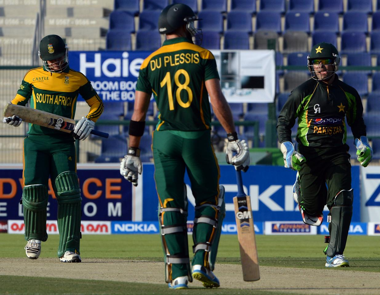 Pakistan's wicket keeper Umar Akmal (R) celebrates after successful stumps of South African batsman Quinton de Kock (L) during the third day-night international in Sheikh Zayed Cricket Stadium in Abu Dhabi on Novemver 6, 2013. South African captain AB de Villiers won the toss and decided to bat in the first. The five-match series is tied at 1-1. AFP PHOTO/ Asif HASSAN        (Photo credit should read ASIF HASSAN/AFP/Getty Images)