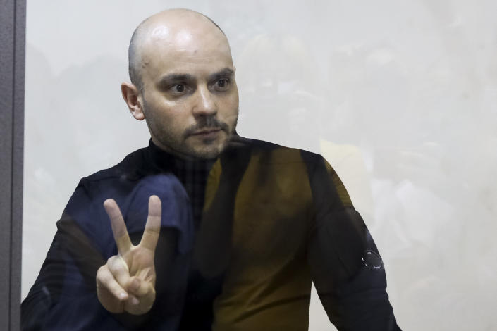 """Andrei Pivovarov, the head of Open Russia movement gestures standing behind the glass during a court session in Krasnodar, Russia, Wednesday, June 2, 2021. In the southern city of Krasnodar, a court was scheduled to consider whether to keep Andrei Pivovarov, the head of the Open Russia movement, in custody pending an investigation. Pivovarov was pulled off a Warsaw-bound plane at St. Petersburg's airport just before takeoff late Monday and taken to Krasnodar, where authorities accused him of supporting a local election candidate last year on behalf of an """"undesirable"""" organization. (AP Photo)"""