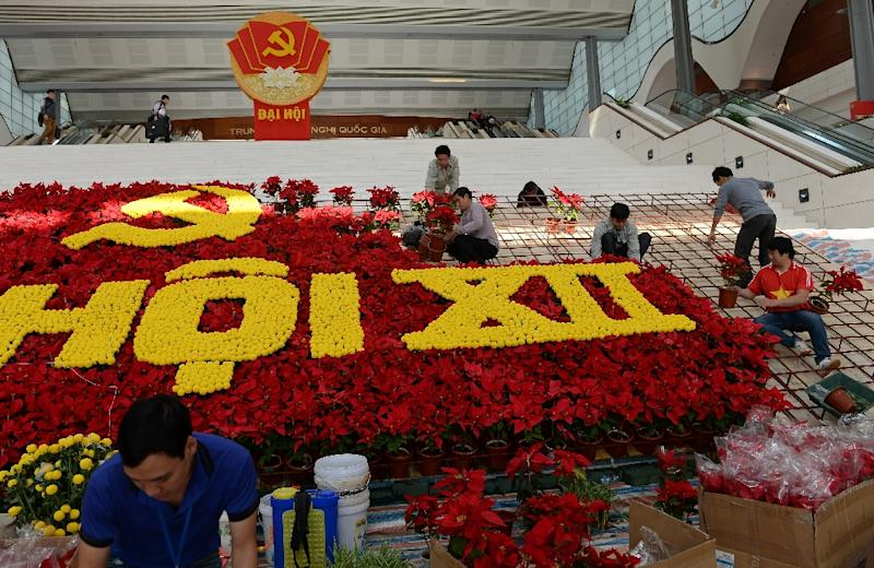 Workers place flowers as they set up decorations at the My Dinh National Convention Center, the main venue of the upcoming Vietnam Communist Party's 12th National Congress, in Hanoi, on January 18, 2016 (AFP Photo/Hoang Dinh Nam)