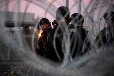 U.S. Customs and Border Protection (CBP) Special Response Team (SRT) officers are seen through concertina wire at the San Ysidro Port of Entry after the land border crossing was temporarily closed to traffic in Tijuana, Mexico November 19, 2018. REUTERS/Adrees Latif