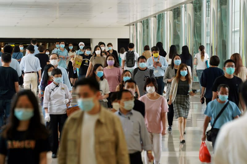 FILE PHOTO: People wearing face masks walk at a shopping mall in Hong Kong