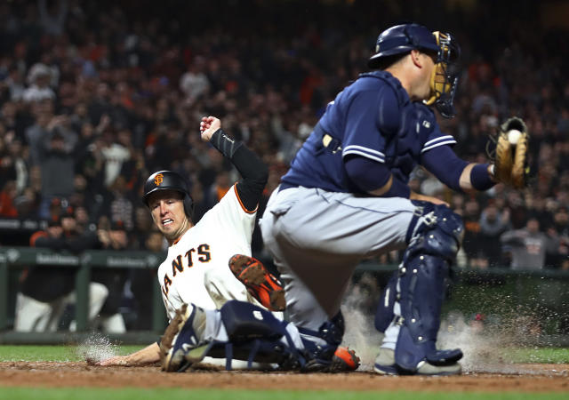 San Francisco Giants' Buster Posey, left, scores next to San Diego Padres catcher A.J. Ellis during the eighth inning of a baseball game Thursday, June 21, 2018, in San Francisco. (AP Photo/Ben Margot)