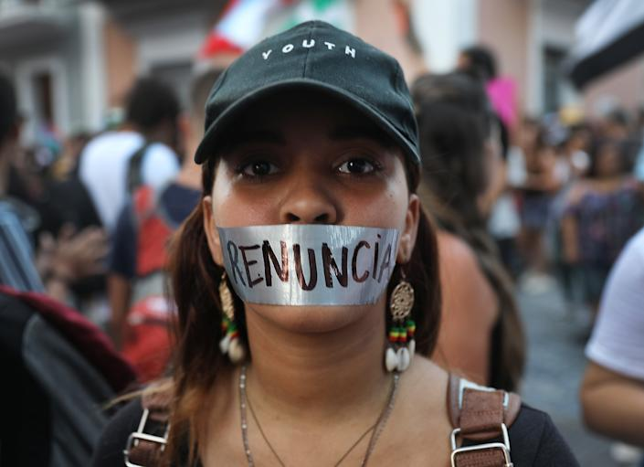 """Maria Linoshka, wearing tape over her mouth reading """"resignation"""" in Spanish, joins with other protesters demonstrating along a street leading to the Governors mansion as they call for Puerto Rican Governor Ricardo Rossello to step down on July 16, 2019 in Old San Juan, Puerto Rico. (Photo: Joe Raedle/Getty Images)"""