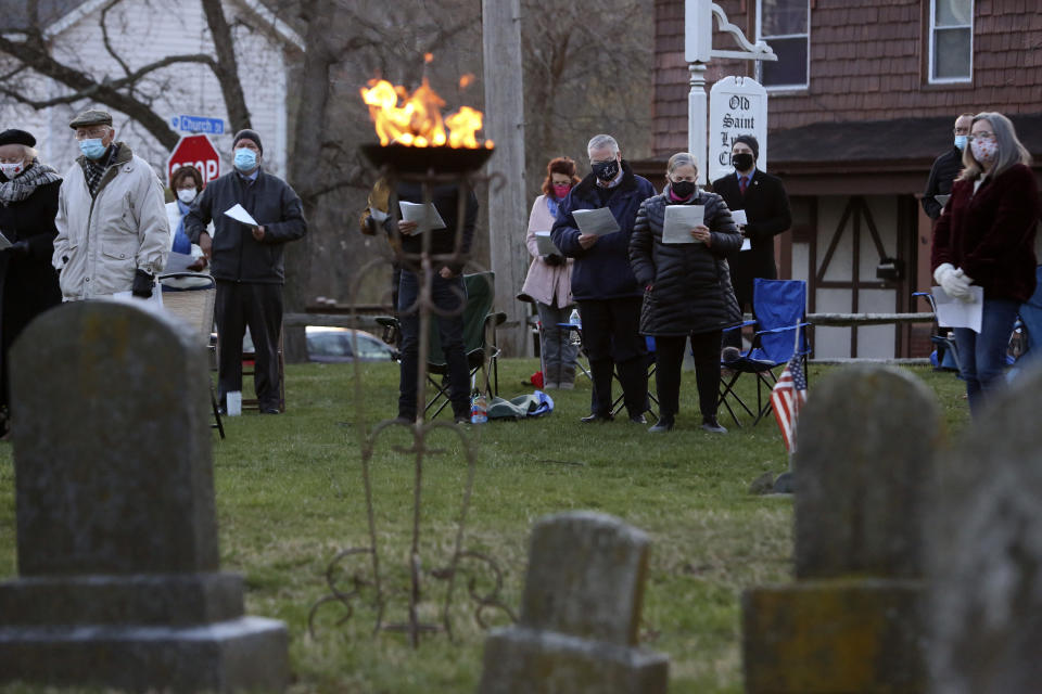 Parishioners of St. Paul's Episcopal Church stand to worship during an Easter sunrise service held on the burial grounds outside of Old St. Luke's Church in Carnegie, Pa., on Sunday, April 4, 2021. For many congregants, this was the first in-person worship service they have attended since the coronavirus surge in November. (AP Photo/Jessie Wardarski)