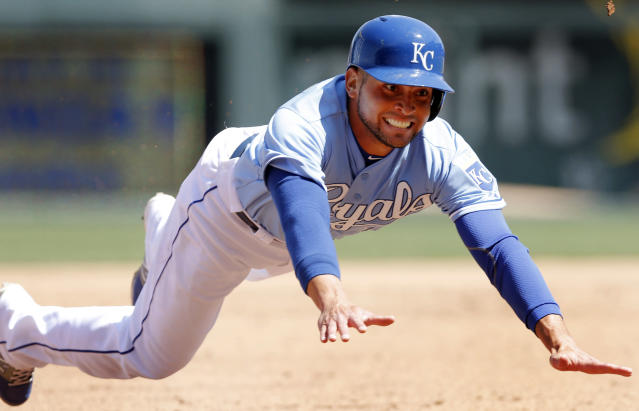 Kansas City Royals' Omar Infante dives for third base on a hit by teammate Eric Hosmer during the fourth inning of a baseball game against the Chicago White Sox at Kauffman Stadium in Kansas City, Mo., Saturday, April 5, 2014. Infante was safe on the play. (AP Photo/Orlin Wagner)