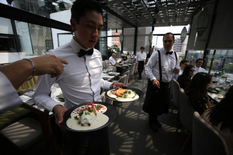 In this Aug. 26, 2019 photo, a waiter delivers chiles en nogada topped with pomegranate seeds, parsley, and walnut sauce to diners at Arango restaurant in Mexico City. It can take hours to make one of the jewels of Mexican gastronomy, decorated in the green, white and red of the country's flag, and the sweet and salty dish is served only in the weeks around Mexico's independence celebrations. (AP Photo/Rebecca Blackwell)