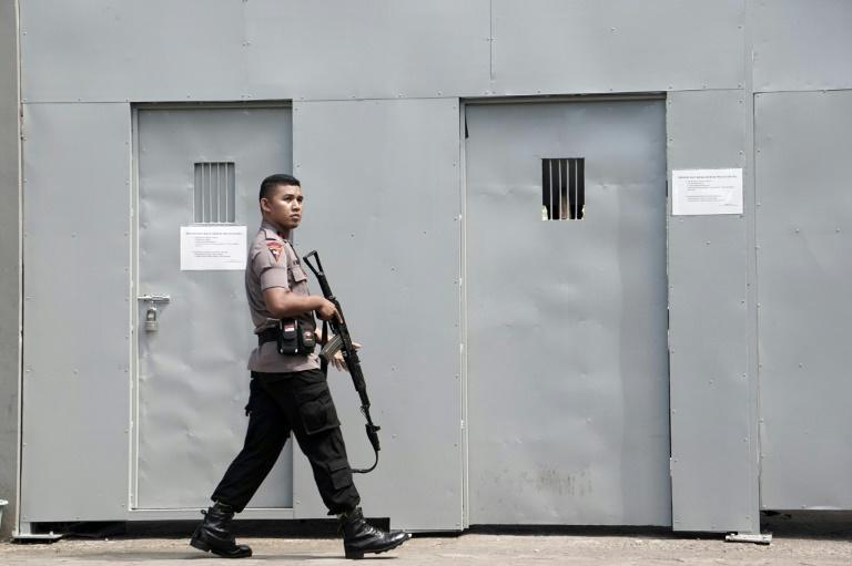 A policeman patrols on July 25, 2016 outside the only entrance to Indonesia's highest security Nusakambangan prison in Cilacap, home to a high-security prison where the country conducts executions