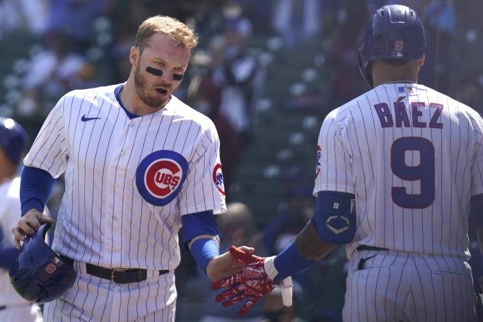 Chicago Cubs' Ian Happ, left, celebrates with teammate Javier Baez after scoring on a single during the first inning of a baseball game against the Pittsburgh Pirates in Chicago, Sunday, April 4, 2021. (AP Photo/Nam Y. Huh)