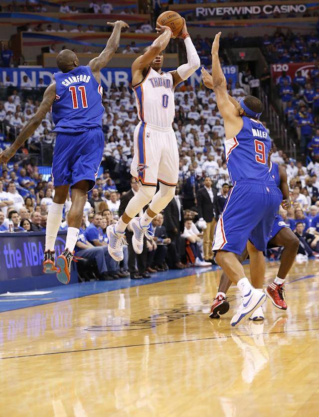 Oklahoma City Thunder guard Russell Westbrook (0) shoots between Los Angeles Clippers guard Jamal Crawford (11) and forward Jared Dudley (9) in the third quarter of Game 2 of the Western Conference semifinal NBA basketball playoff series in Oklahoma City, Wednesday, May 7, 2014. Oklahoma City won 112-101. (AP Photo/Sue Ogrocki)