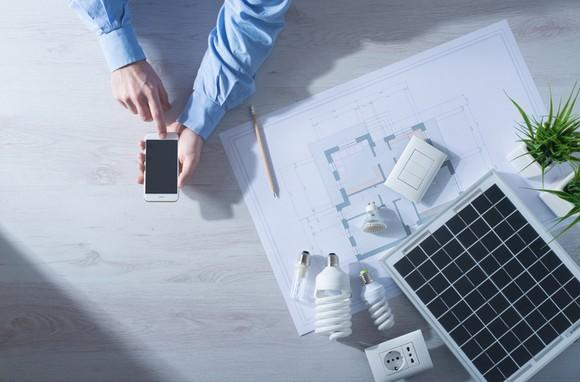 A man checking his smartphone at a desk with a small solar panel and architectural drawings sitting on it.