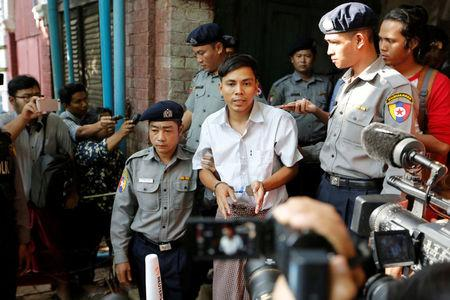 Detained Reuters journalist Kyaw Soe Oo speaks to the media, while escorted by police, after a court hearing in Yangon, Myanmar May 22, 2018. REUTERS/Ann Wang