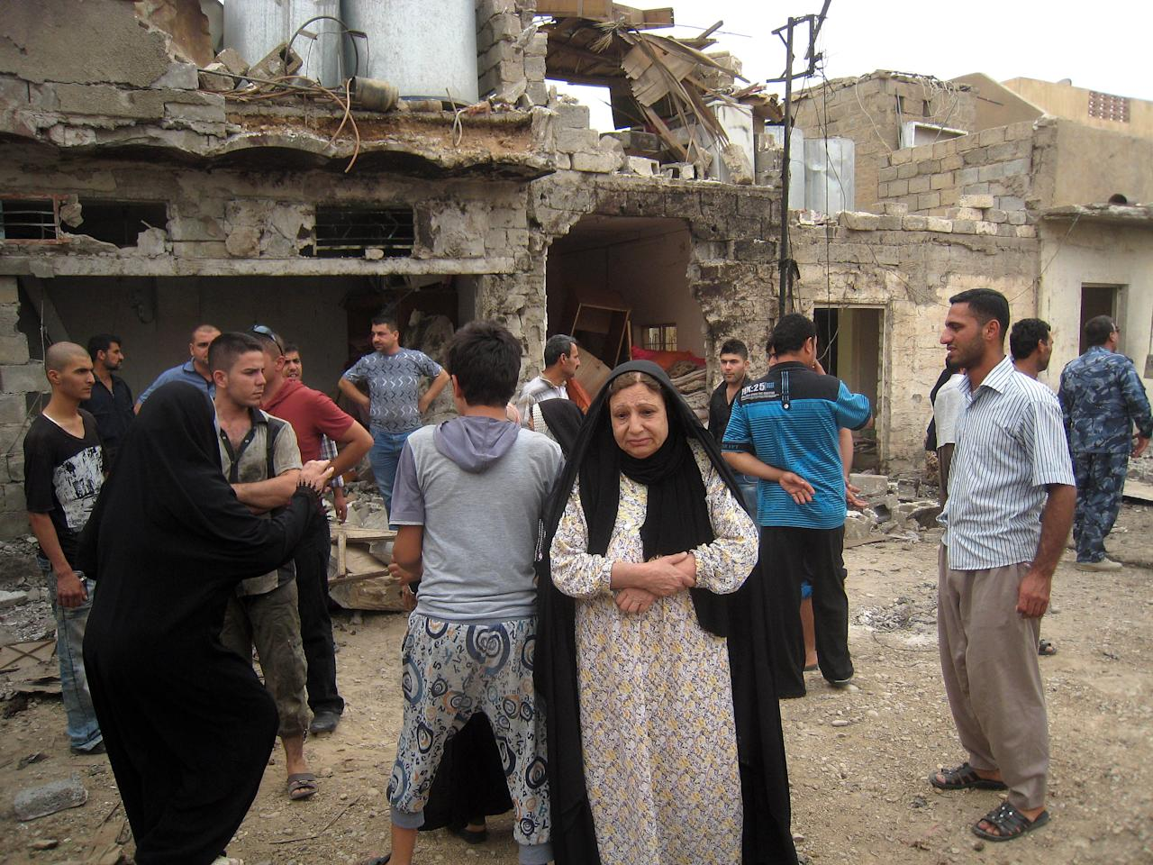 Residents react to a car bomb attack in Kirkuk, 180 miles (290 kilometers) north of Baghdad, Iraq, Wednesday, May 15, 2013. Two car bombs struck a disputed northern Iraqi city on Wednesday as a series of attacks across the country, killing and wounding dozens of people, police said. (AP Photo/Emad Matti)