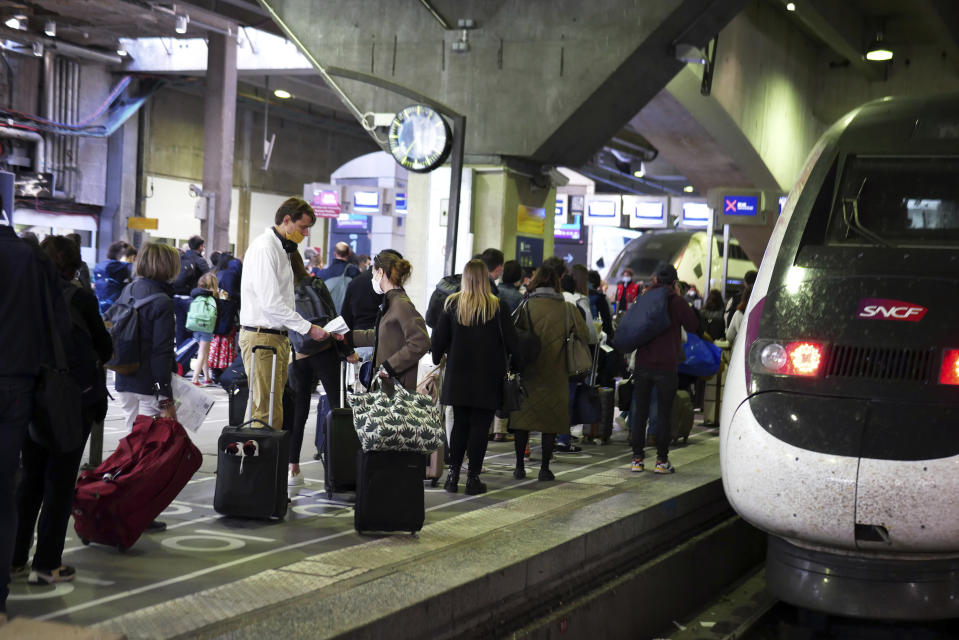 """Travelers wait to board a train at the Montparnasse railway station, in Paris, Friday, April 2, 2021. With France now Europe's latest virus danger zone, Macron on Wednesday ordered temporary school closures nationwide and new travel restrictions. But he resisted calls for a strict lockdown, instead sticking to his """"third way"""" strategy that seeks a route between freedom and confinement to keep both infections and a restless populace under control until mass vaccinations take over. (AP Photo/Thibault Camus)"""