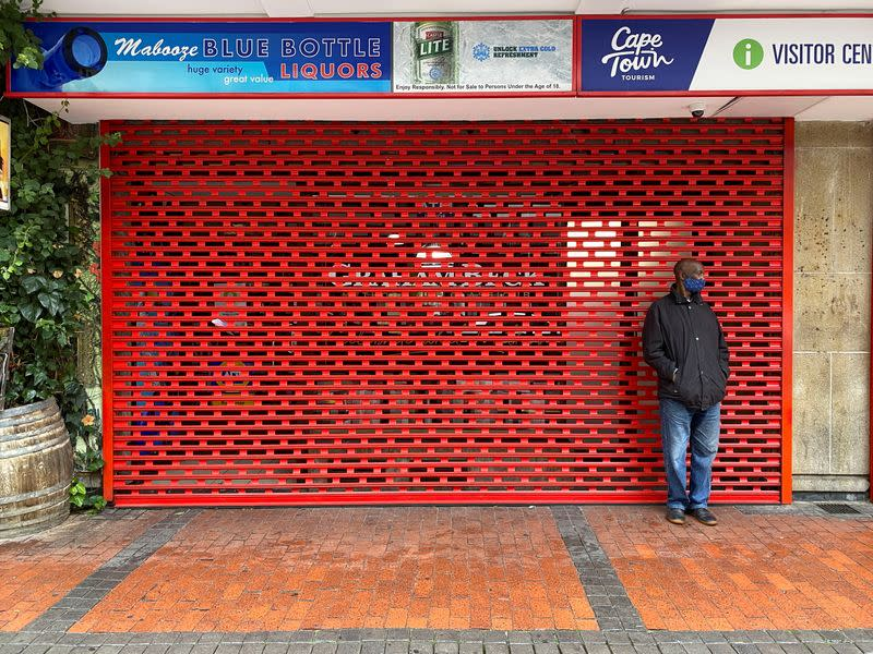 Man stands outside a shuttered liquor store as new COVID-19 restrictions take effect in Cape Town