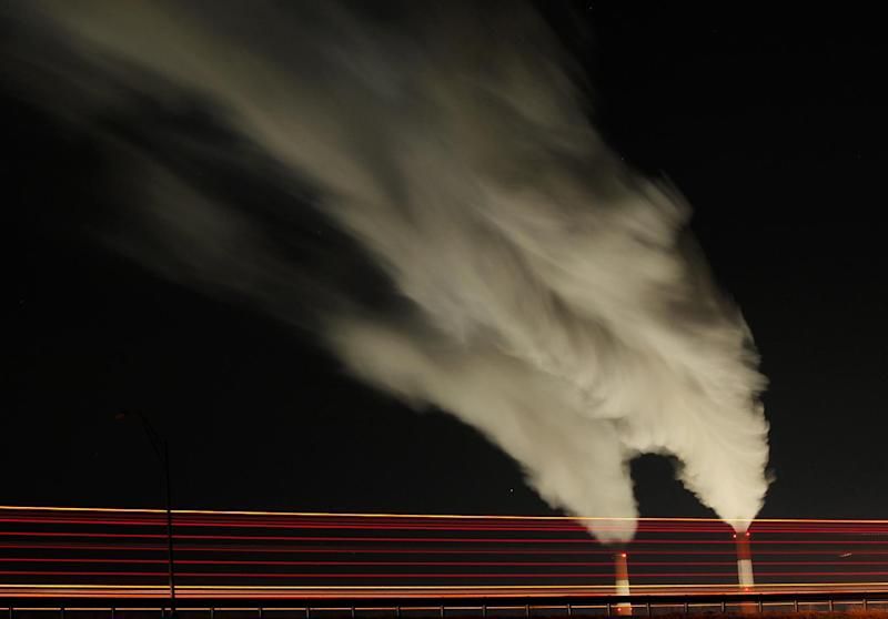 """FILE - In this Jan. 19, 2012 file photo, smoke rises in this time exposure image from the stacks of the La Cygne Generating Station coal-fired power plant in La Cygne, Kan. The United Nations climate chief is urging people not to look solely to their governments to make tough decisions to slow global warming, and instead to consider their own role in solving the problem. Approaching the half-way point of two-week climate talks in Doha, Christiana Figueres, the head of the U.N.'s climate change secretariat, said Friday, Nov. 30, 2012 that she didn't see """"much public interest, support, for governments to take on more ambitious and more courageous decisions.""""(AP Photo/Charlie Riedel, File)"""