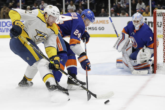 Nashville Predators' Yakov Trenin (32) fights for control of the puck with New York Islanders' Scott Mayfield (24) as goaltender Thomas Greiss (1) watches during the first period of an NHL hockey game Tuesday, Dec. 17, 2019, in Uniondale, N.Y. (AP Photo/Frank Franklin II)