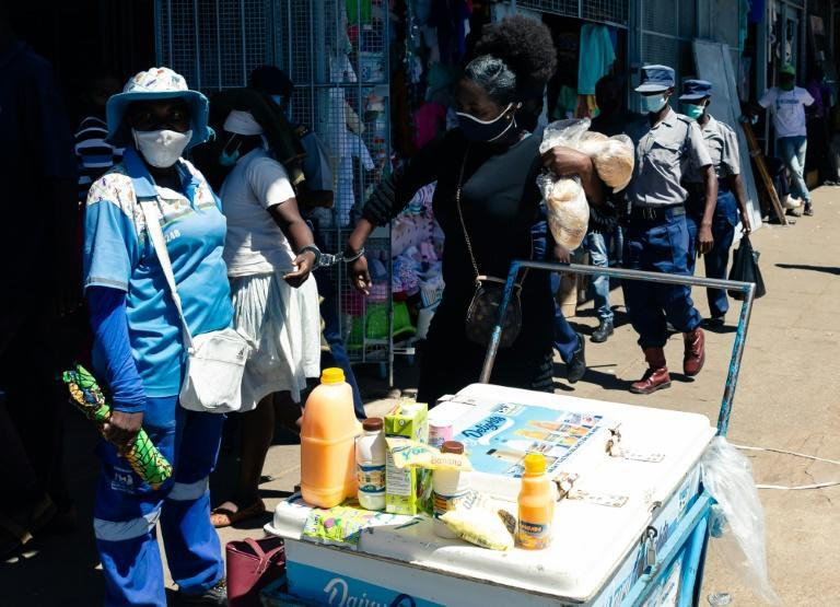Spiwe Tembo, an informal trader who makes her living selling buns, is handcuffed to another vendor after being arrested by police in Harare