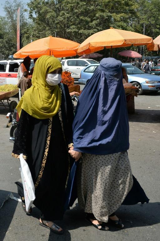 Women hold hands as they walk at a market area in Kabul on September 1, 2021 (AFP/HOSHANG HASHIMI)