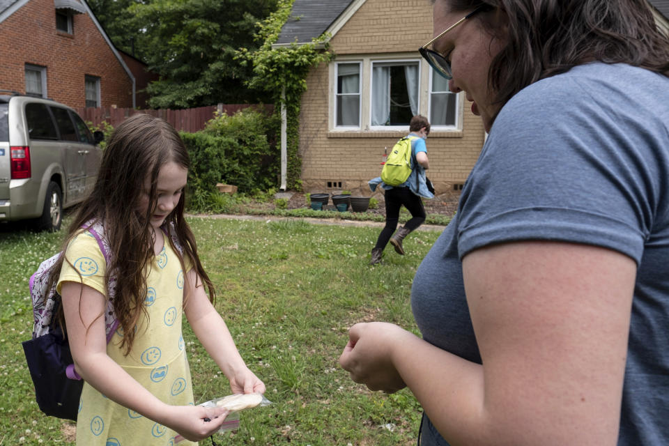 Abby Norman, right, looks at a project made by her daughter Priscilla, 9, left, as Juliet, 11, runs inside as they arrive home from school to the family's home in Decatur, Ga., Tuesday, May 18, 2021. Priscilla was in tears the first morning of school testing this year because she felt pressure to do well, but didn't feel prepared after remote learning. (AP Photo/Ben Gray)