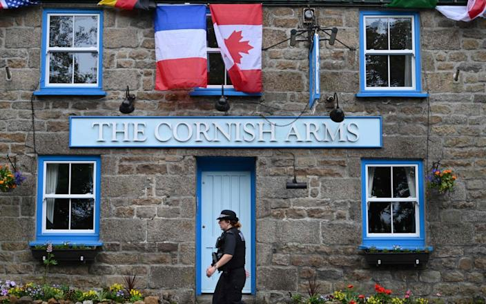 A British police officer walks past The Cornish Arms gastropub in St Ives - AFP