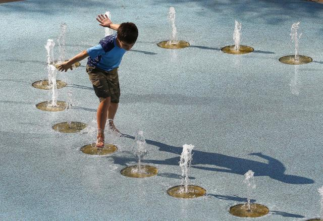 <p>One person uses the CityScape splash pad to stay cool as temperatures climb to near-record highs, June 20, 2017, in Phoenix. (Ross D. Franklin/AP) </p>