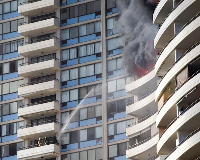 <p>Firefighters on a lower balcony spray water upwards while trying to contain a fire at the Marco Polo apartments, Friday, July 14, 2017, in Honolulu, Hawaii. (Photo: Marco Garcia/AP) </p>