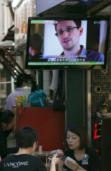 A TV screen shows the news of Edward Snowden, former CIA employee who leaked top-secret documents about sweeping U.S. surveillance programs, at a restaurant in Hong Kong Wednesday, June 12, 2013. The whereabouts of Snowden remained unknown Wednesday, two days after he checked out of a Hong Kong hotel. (AP Photo/Kin Cheung)