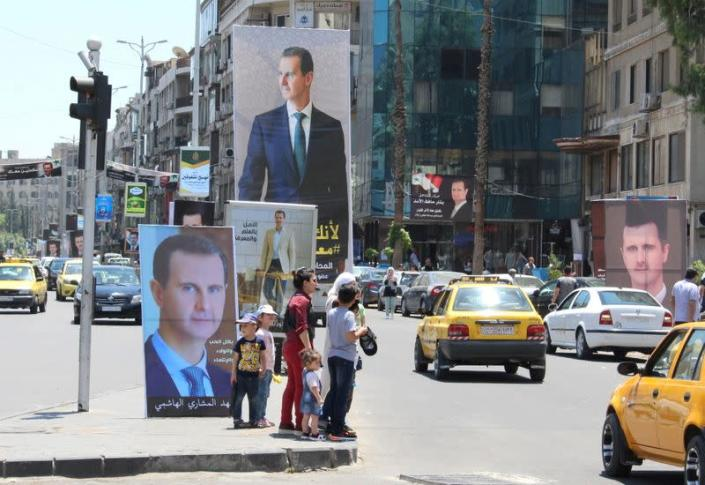 FILE PHOTO: People stand near posters depicting Syria's President Bashar al-Assad in Damascus