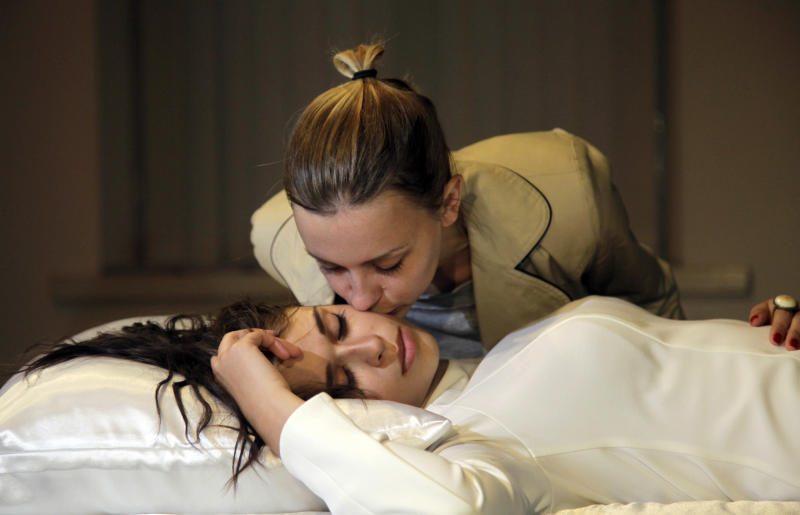 A visitor kisses sleeping women during a new art project called 'Sleeping Beauties' created by a Canadian-Ukrainian artist Taras Polataiko in The National Art Museum in Kiev, Ukraine, Friday, Sept. 7, 2012. Five young Ukrainian women, dressed in white wedding gowns, take turns sleeping on display in the museum for a couple of hours every day. Based on the fairytale 'Sleeping Beauty', the idea of the art-exhibition is for visitors to look at a sleeping girl, and, if they feel the urge, kiss her on the lips. If a sleeping beauty opens up her eyes she's obliged by a legal contract to marry. (AP Photo/Efrem Lukatsky)