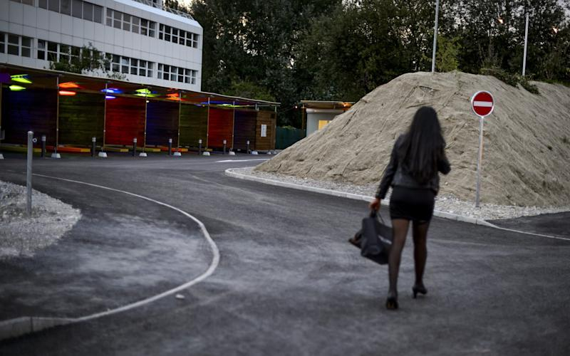 """A prostitute walks past so-called """"sex boxes"""" at the opening day of Switzerland's first sex drive-in on August 26, 2013 in Zurich, which is aiming to get prostitution off the city streets. The drive-in, which as darkness began to fall was bathed in colourful lights, has a track where the sex workers can show off their assets and negotiate a price, and nine so-called """"sex boxes"""" where they and their clients can park and conclude the transaction. AFP PHOTO / FABRICE COFFRINI (Photo credit should read FABRICE COFFRINI/AFP/Getty Images) - FABRICE COFFRINI/AFP"""