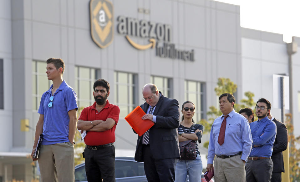 People wait in a line of about one hundred applicants waiting to enter a job fair Wednesday, Aug. 2, 2017, at an Amazon fulfillment center, in Kent, Wash. Amazon plans to make thousands of job offers on the spot at nearly a dozen U.S. warehouses during the recruiting event. (AP Photo/Elaine Thompson)