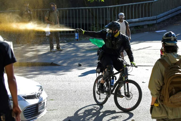"""A Seattle police officer on a bicycle deploys pepper spray in clashes with protesters following a """"Youth Day of Action and Solidarity with Portland"""" demonstration (AFP Photo/Jason Redmond)"""