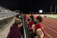 El Modena cheerleaders Destinee Cerda, right, and Soraya Granados chat with their mothers over a fence to encourage social distancing during the team's high school football game with El Dorado in Orange, Calif., Friday, March 19, 2021. (AP Photo/Jae C. Hong)