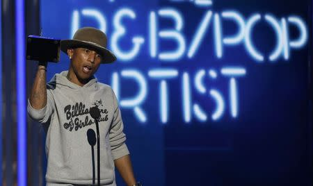 Pharrell Williams accepts the award for best male R&B/pop artist during the 2014 BET Awards in Los Angeles