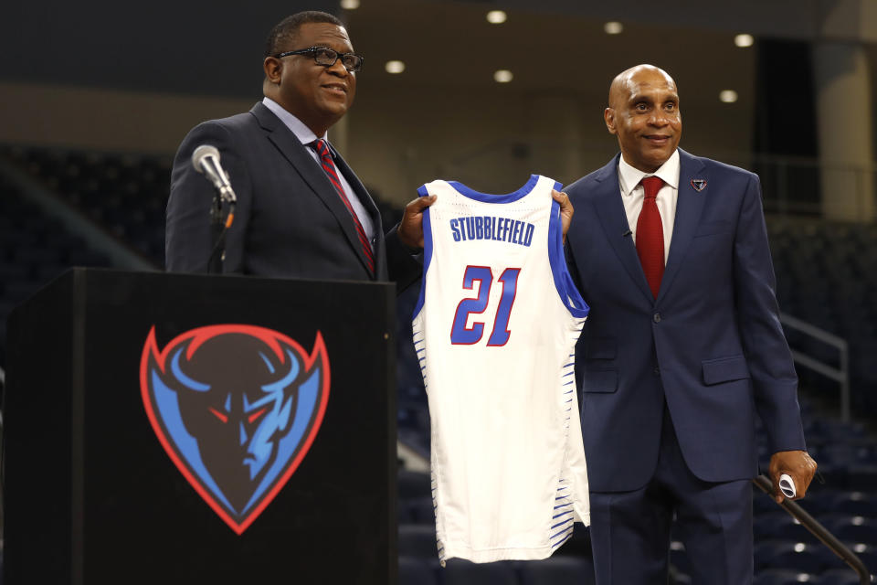 DePaul University's new men's basketball head coach Tony Stubblefield holds a jersey accompanied by director of athletics DeWayne Peevy, left, during a press conference, Wednesday, April 7, 2021 in Chicago. (AP Photo/Shafkat Anowar)