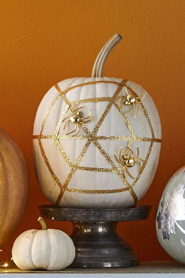 """<p>Spray paint your pumpkin white and let dry, then hot-glue three long strips of ¼-inch glittered ribbon to to create radial threads of web. Measure, cut, and glue 12 shorter ribbon strips to complete the web. Spray paint several fake spiders gold, the hot-glue to your """"web.""""</p><p><a class=""""link rapid-noclick-resp"""" href=""""https://www.amazon.com/Muzboo-Realistic-Plastic-Halloween-Decorations/dp/B07CVJ3LBN?tag=syn-yahoo-20&ascsubtag=%5Bartid%7C10070.g.1902%5Bsrc%7Cyahoo-us"""" rel=""""nofollow noopener"""" target=""""_blank"""" data-ylk=""""slk:SHOP FAKE SPIDERS"""">SHOP FAKE SPIDERS</a> </p>"""