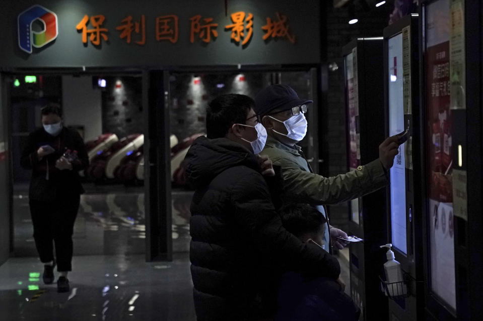 People wearing face masks to help curb the spread of the coronavirus collect their movie tickets at Poly Cinema in Beijing on Thursday, Feb. 25, 2021. With coronavirus well under control in China and cinemas running at half capacity, moviegoers are smashing China's box office records, setting a new high mark for ticket sales in February, with domestic productions far outpacing their Hollywood competitors. (AP Photo/Andy Wong)