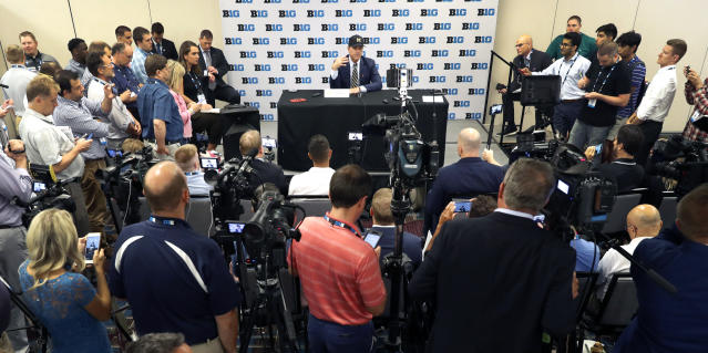 Michigan head coach Jim Harbaugh, back center, is surrounded by reporters and photographers during the Big Ten Conference NCAA college football media days Friday, July 19, 2019, in Chicago. (AP Photo/Charles Rex Arbogast)