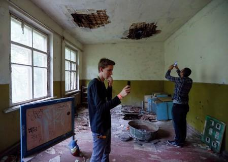 Visitors take pictures at a kindergarten in the abandoned village of Kopachi, near the Chernobyl Nuclear Power Plant