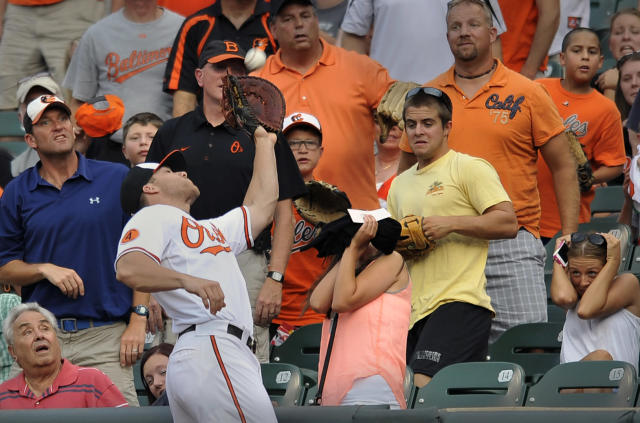 Baltimore Orioles first baseman Chris Davis reaches into the crowd to catch a foul ball hit by Houston Astros' Jose Altuve in the first inning of a baseball game on Wednesday, July 31, 2013, in Baltimore. (AP Photo/Gail Burton)