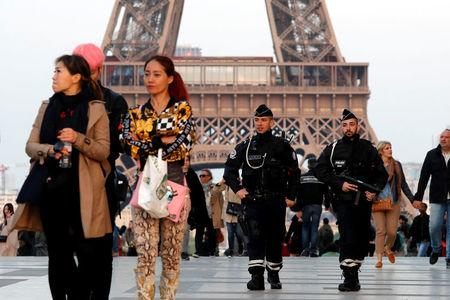Police patrol at the Trocadero near the Eiffel Tower after a policeman was killed and two others were wounded in a shooting incident in Paris, France, April 21, 2017. REUTERS/Charles Platiau