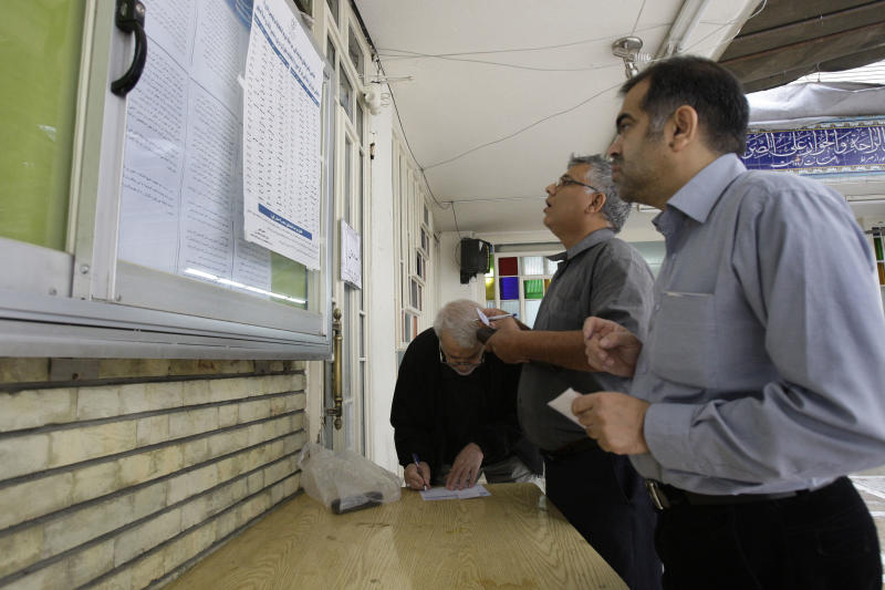 Iranian voters check the list of the candidates and fill in the ballots in the parliamentary runoff elections at a polling station in Tehran, Iran, Friday, May 4, 2012. The country has begun runoff elections for more than one-fifth of parliamentary seats. Friday's report says 130 hopefuls will compete for 65 seats in 33 constituencies including the capital Tehran with 25 undecided seats. (AP Photo/Vahid Salemi)