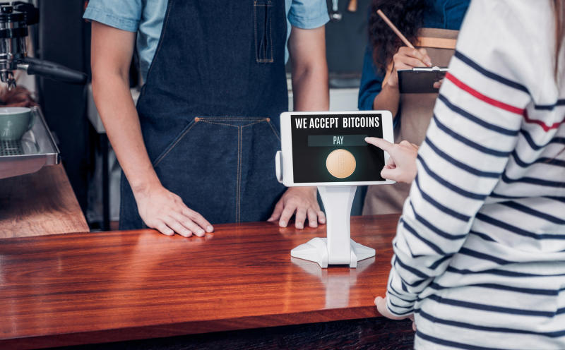 A customer using a point-of-sale device that accepts bitcoin.