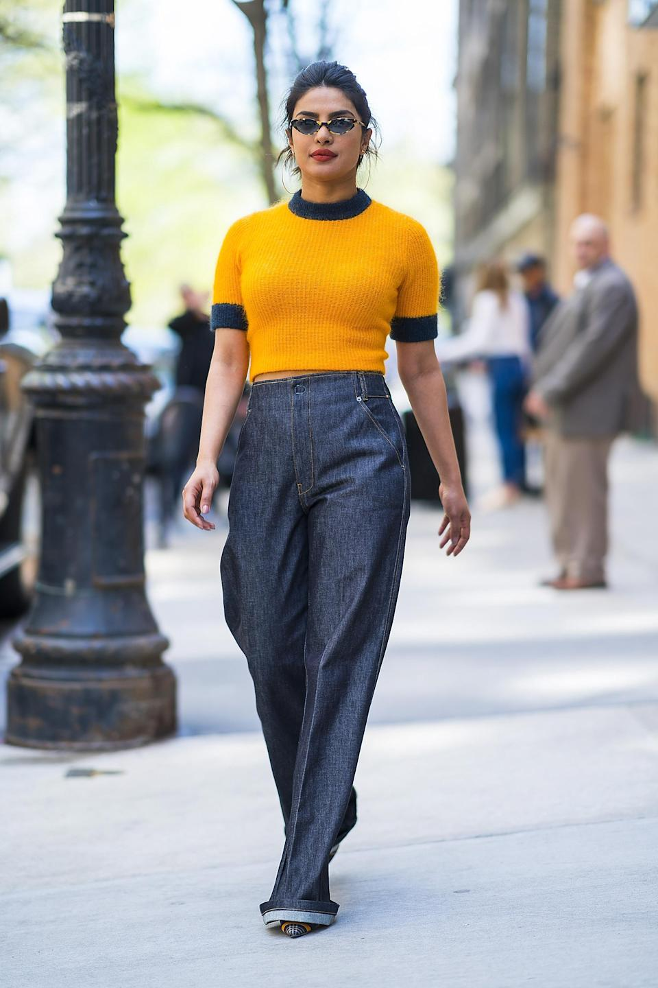 <p>Actress Priyanka looked too cool for school while dashing from meetings in New York wearing a tangerine-coloured, cropped fluffy jumper by Ganni with high-waisted, wide-legged trousers and some slim sunnies.<br><em>[Photo: Getty]</em> </p>