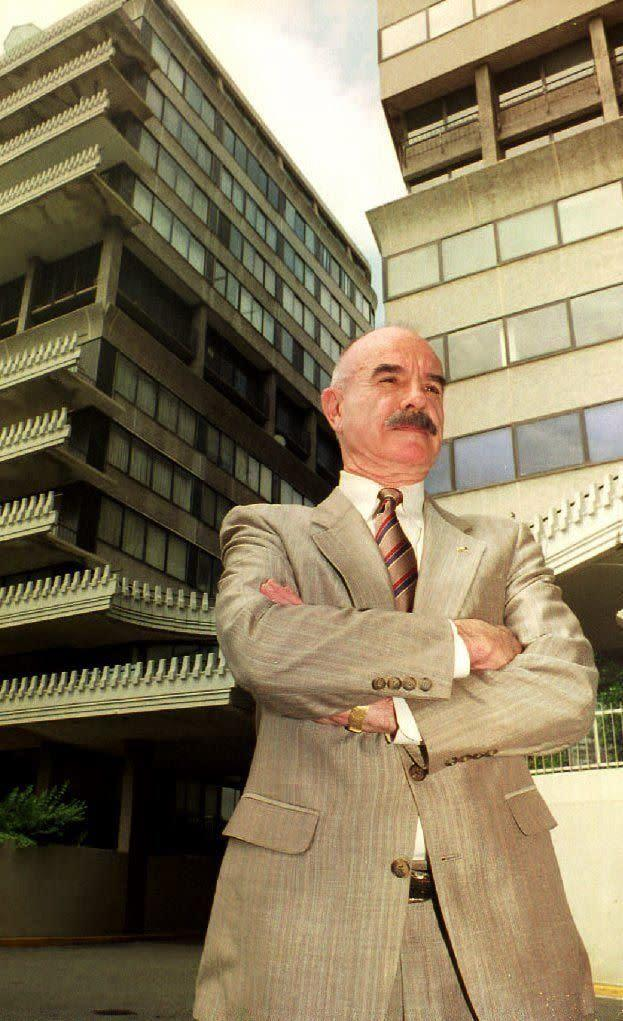 G. Gordon Liddy, former assistant to former U.S. President Richard Nixon, stands in front of the Watergate office complex 17 June 1992. Liddy, who has a daily radio talk show, broadcasted live from the site to mark the 20th anniversary of the Watergate break-in. Liddy was a key collaborator in the break-in and served a five-year prison sentence for his role in the crime. (Photo credit should read BENJAMIN RUSNAK/AFP/GettyImages)