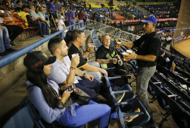 A man sells beer during the opening winter season game between Leones de Caracas and Tigres de Aragua in Caracas, Venezuela, Tuesday, Nov. 5, 2019. Despite a noticeable number of empty seats, the game didn't disappoint. The Tigers beat the Lions of Caracas 6-3. (AP Photo/Ariana Cubillos)